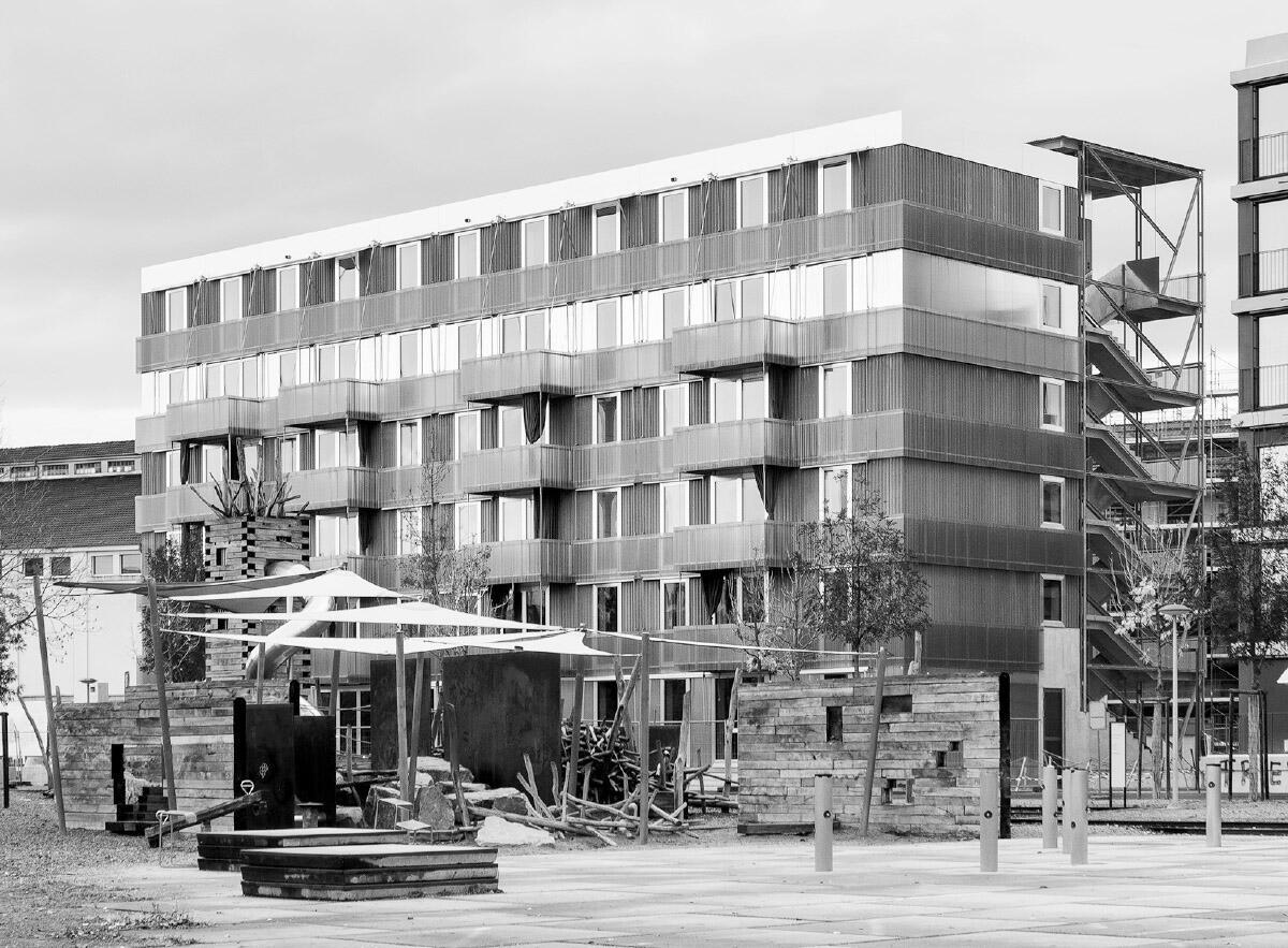 Rohe, industrielle Materialien in horizontaler Bänderung charakterisieren das Äussere des Genossenschaftshauses. Die sperrholzbeplankten Wohnküchen liegen am gemeinschaftlich genutzten Laubengang. Geschosshohe Türen und Fensteröffnungen verschaffen Durchblicke vom Hof zum Park.  Bild: Rory Gardiner