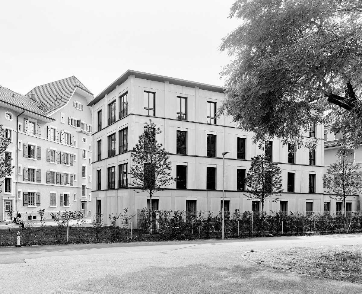 Der Neubau in Holz-Elementbauweise ordnet sich in Volumen und Ausdruck der historischen Siedlung unter und schliesst den Hofraum zur Strasse hin ab. Im Sockelgeschoss ist eine Demenzwohngruppe untergebracht. Bilder: Alexander Jaquemet