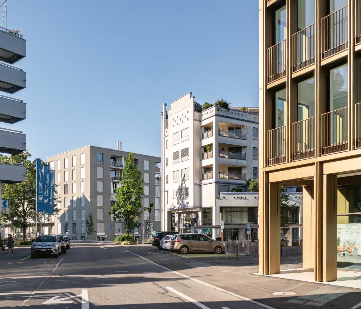Dank seinem städtischen Massstab verbindet das neue Stadthaus von Kriens mit seiner zart proportionierten Aluminiumfassade die Einzelbauten des Bestands zum Ensemble. Bild: Roman Keller