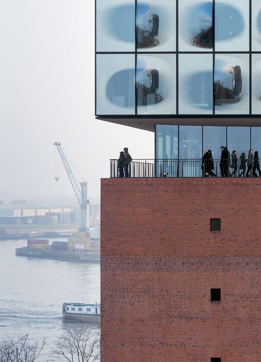 Zwischen dem Dach des massiven Speichers und dem gläsernen Aufbau umrunden die Besucher die Plaza der Elbphilharmonie an der frischen Luft und geniessen die Ausblicke.