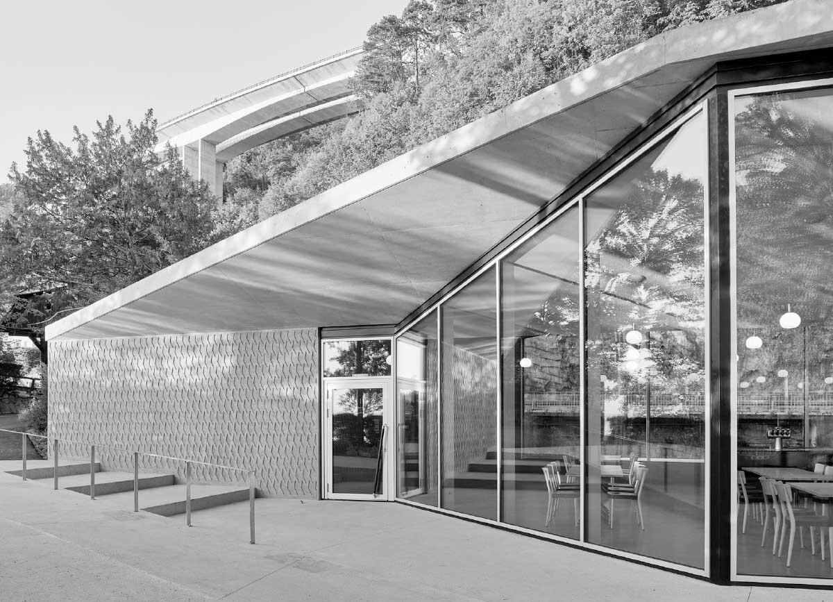 Avec son toit papillon s'ouvrant des deux côtés, lac et montagne, le pavillon crée un geste d'ouverture et d'accueil. Alliant minéralité et légèreté, il réunit les teintes du site avec un programme contemporain. Photo: Ariel Huber