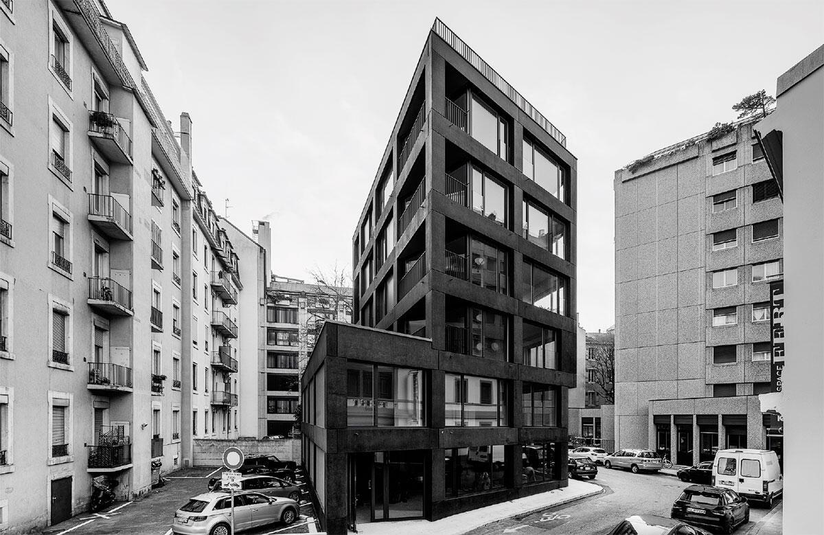 Die tektonische Fassadengliederung bindet auch die vorgeschriebene, fensterlose Brandmauer in den Massstab des Wohnhauses Immeuble Rue Barton, Genève ein.