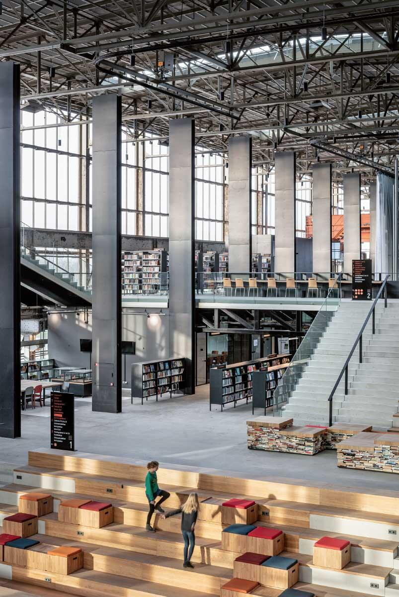 Ein «Bücherberg» füllt den Innenraum der einstigen Montagehalle. Auf ihm lässt es sich über Generationen und Klassen hinweg chatten und schmökern. Bild: Stijn Bollaert