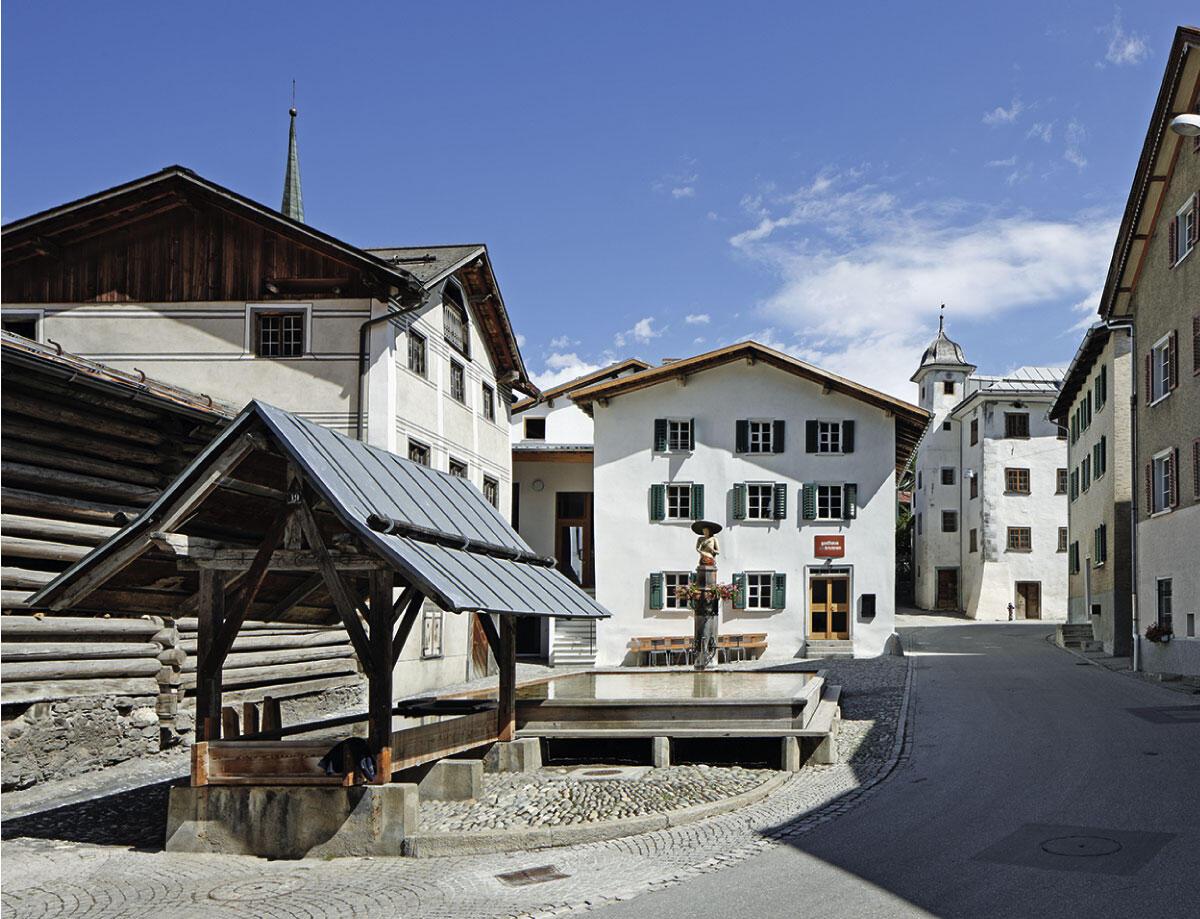 Der hölzerne Brunnen dominiert den Dorfplatz von Valendas und verleiht dem Gasthaus seinen Namen.