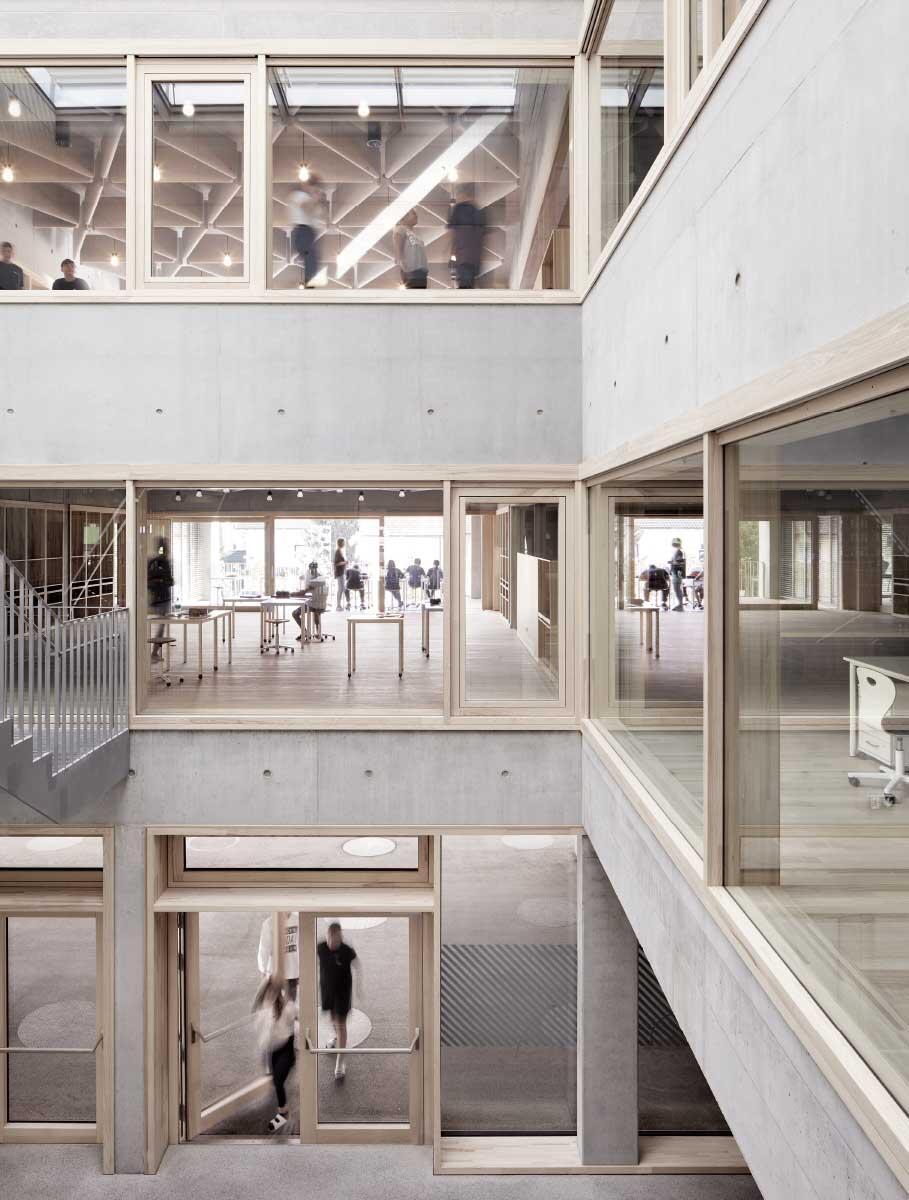 Kontrollierte Transparenz: Blick durch die zentrale Halle in zwei Cluster (sogenannte «Häuser») und den Eingangsbereich im Erdgeschoss. Bild: Adolf Bereuter