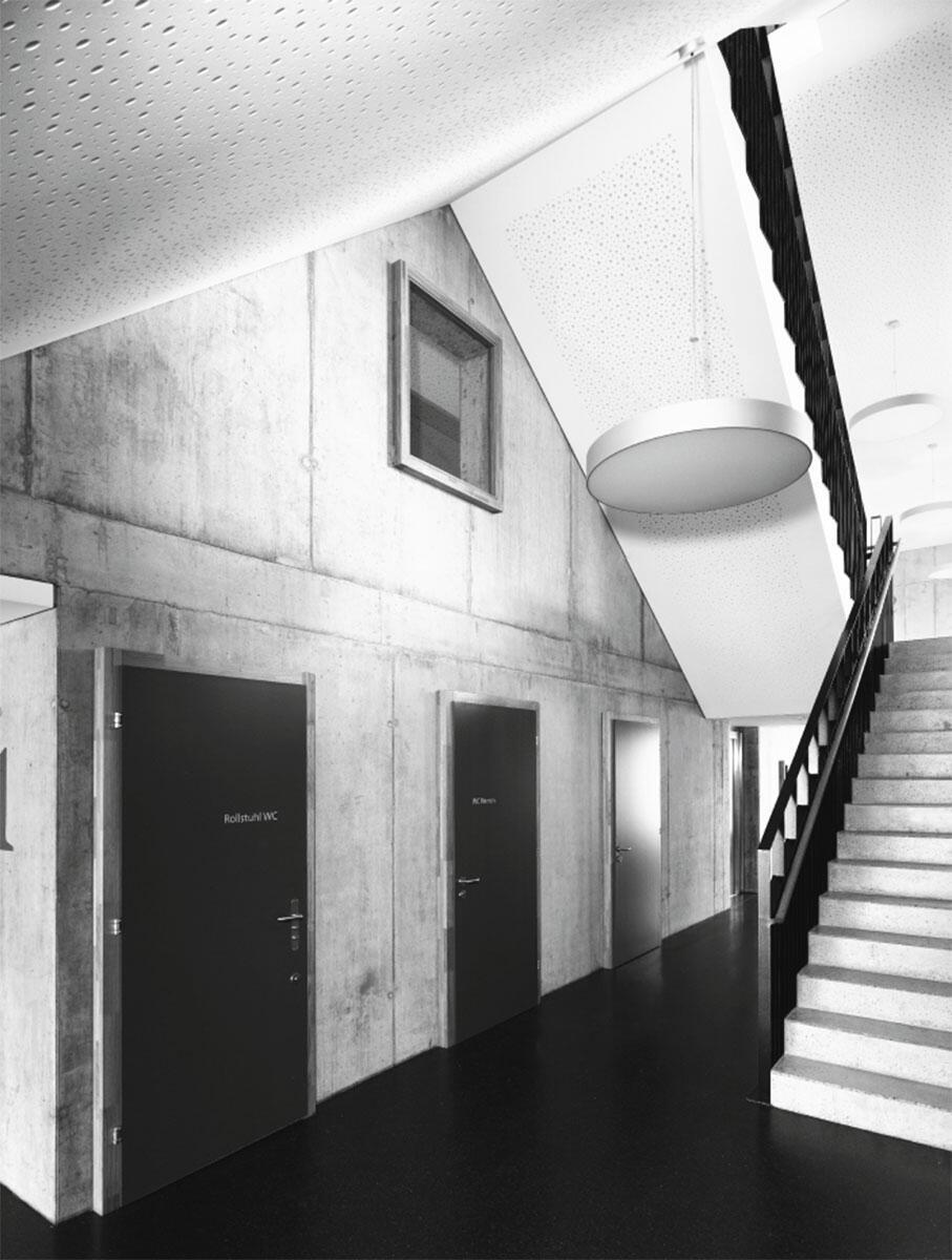 Die Betonhülle des Primarschulhauses Buttisholz ist auch im Innern präsent. Zusammen mit dem Industrieparkett prägt dies den Werkstattcharakter der Schule, der mit Ausblicken durch spielerisch angeordnete Fenster ergänzt wird.