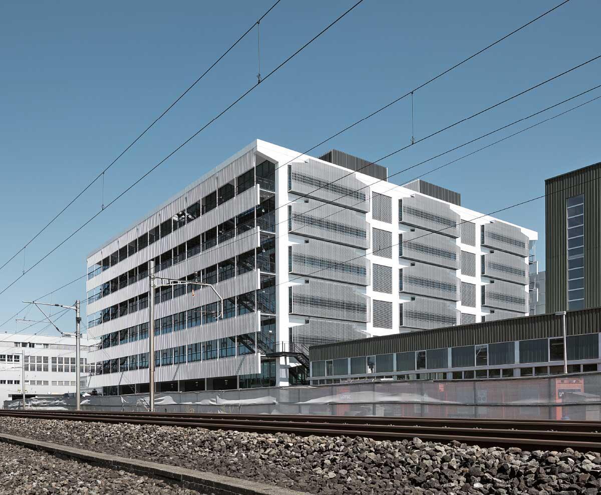Eine durchscheinende, vorgehängte weisse Fassadenschicht verhüllt als Brise-soleil die Längsfassaden des Neubaus; quer dazu prägt das Tragwerk das äussere Bild: Hier kann der Bau beliebig verlängert werden. Bild: Dominique Marc Wehrli