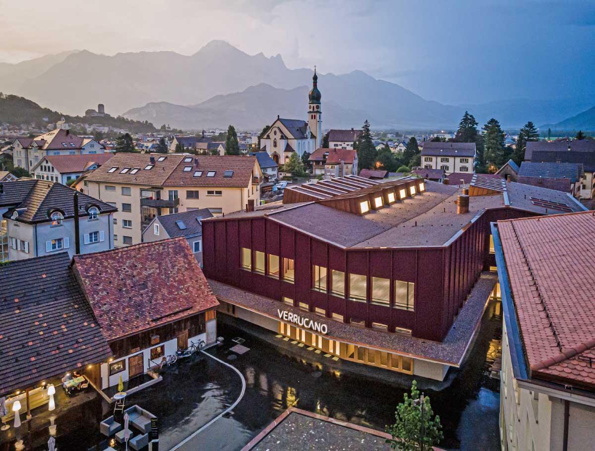 Das aus Holz gebaute Kulturzentrum besetzt die Mitte des Dorfs. Der neue Rathausplatz davor verbindet sich mit dem Hauptplatz des alten Dorfkerns. Bild: Ladina Bischof