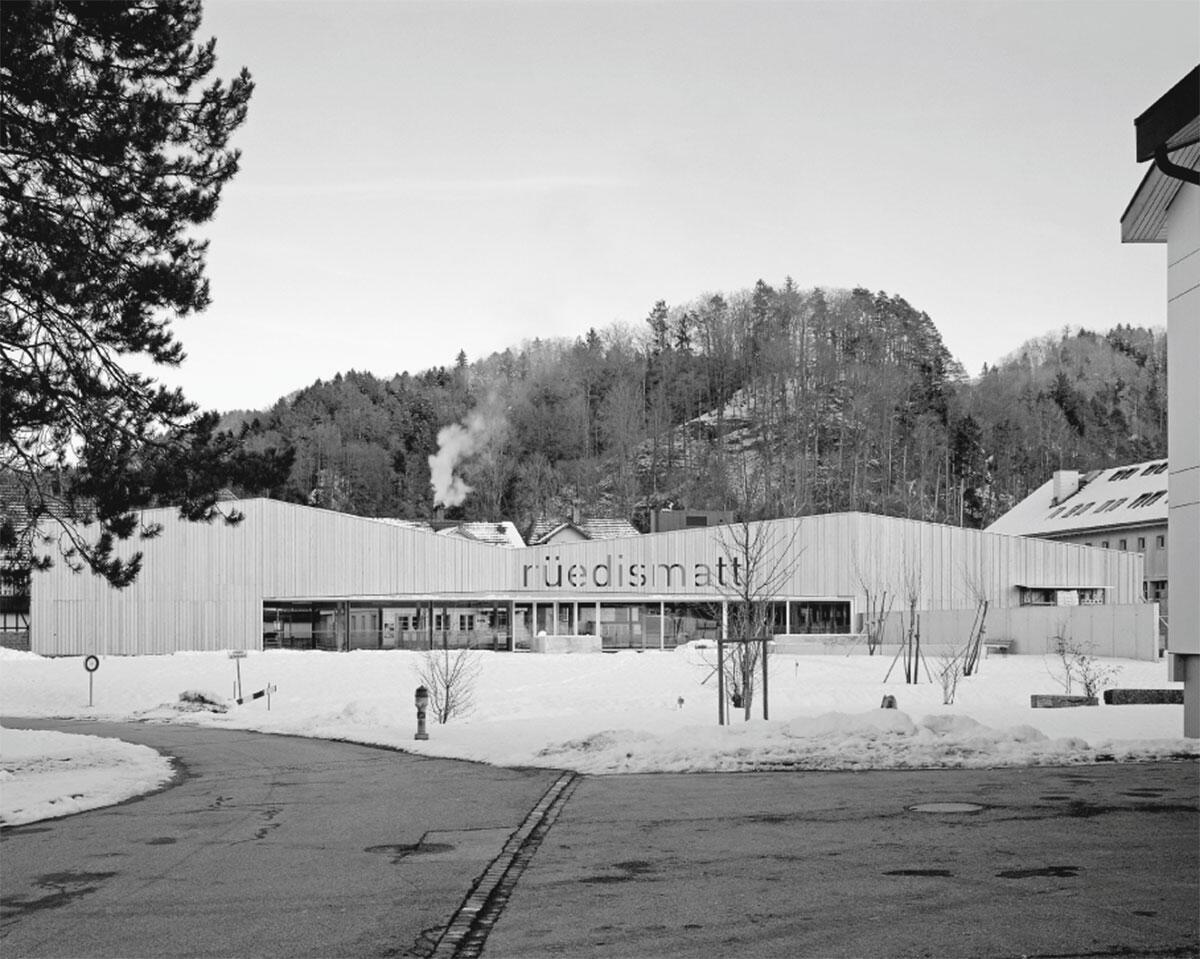 Blick vom bestehenden Schulhaus über den Festplatz auf das neue Dorfzentrum Rüedismatt im Krauchtal von wahlirüefli Architekten und Raumplaner, Biel.
