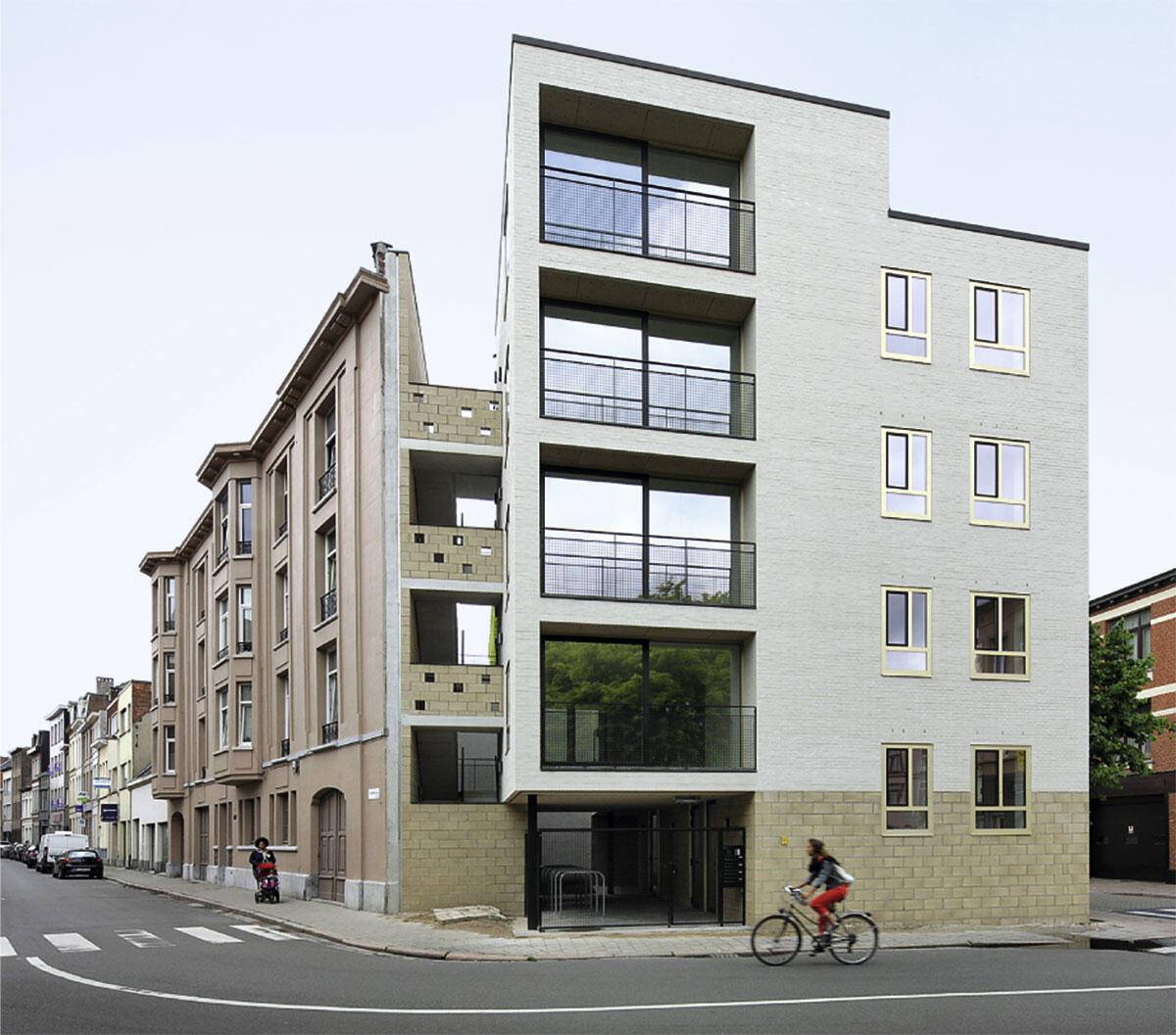 Mehrfamilienhaus in Borgerhout/Antwerpen: Das Eckhaus mit vier Etagenwohnungen schliesst einen Bestandsblock in spitzem Winkel und schafft ein Gesicht für den kleinen Platz davor.