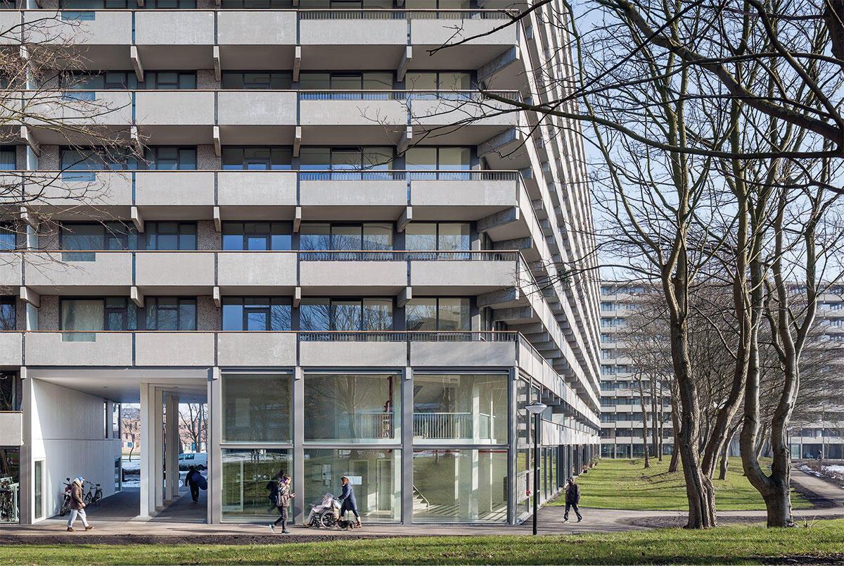 Grosszügige Durchgänge, zweigeschossige Eingangshallen und ein bewohnter Sockel verankern den Giganten im Quartier; die farbliche  Vereinheitlichung der Fassade gibt ihm ein Gesicht. Bild: Stijn Brakkee