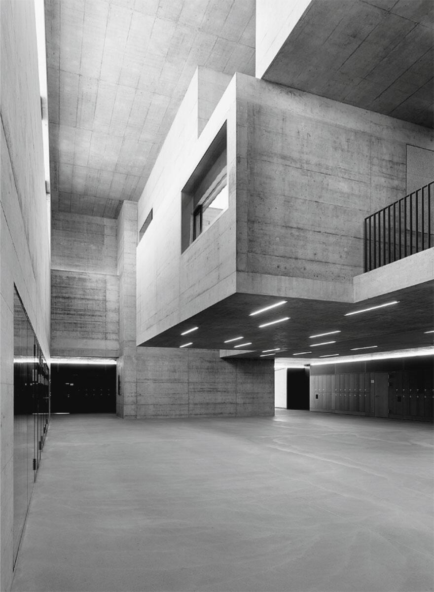 Das dramatisch inszenierte Foyer schiebt sich zwischen Altbau und Erweiterung. Schulhauserweiterung in Kerzers von Cornelius Morscher.