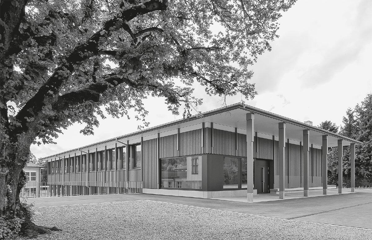 Selbstbewusst und bescheiden zugleich schmiegt sich der Holzbau ins abfallende Gelände. Primarschule Thundorf von Lauener Baer Architekten.