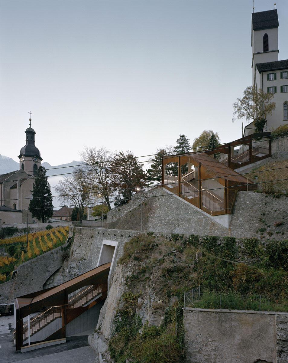 Die Treppen- und Liftanlage im Kontext der Kathedrale (links) und der Kirche St. Luzi.