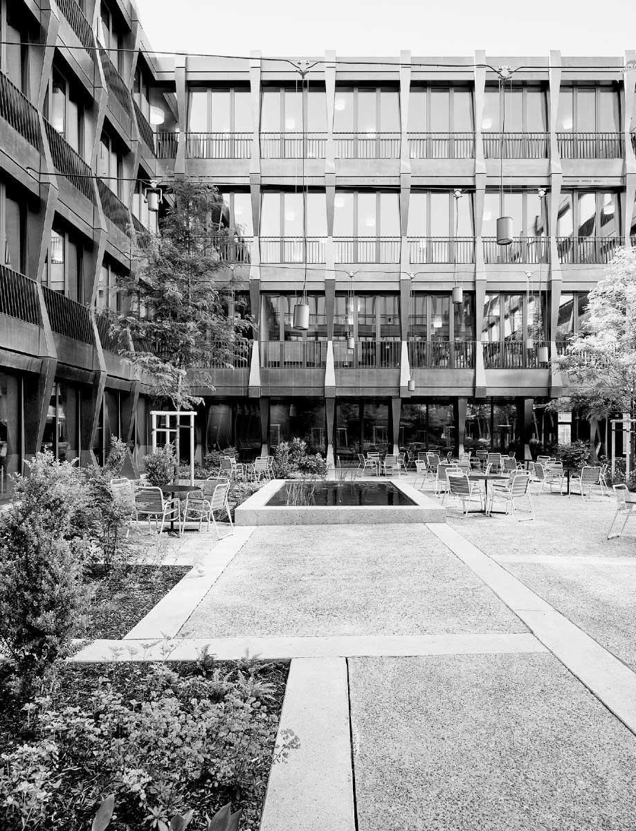 Der Gartenhof bietet zusätzlichen Aufenthaltsraum im Freien, während die Messingfassade sich ähnlich wie zum Strassenraum gibt. Im Inneren öffnen sich die Cafeteria und die Lounge ebenerdig zum Hof. Bild: Kuster Frey Fotografie