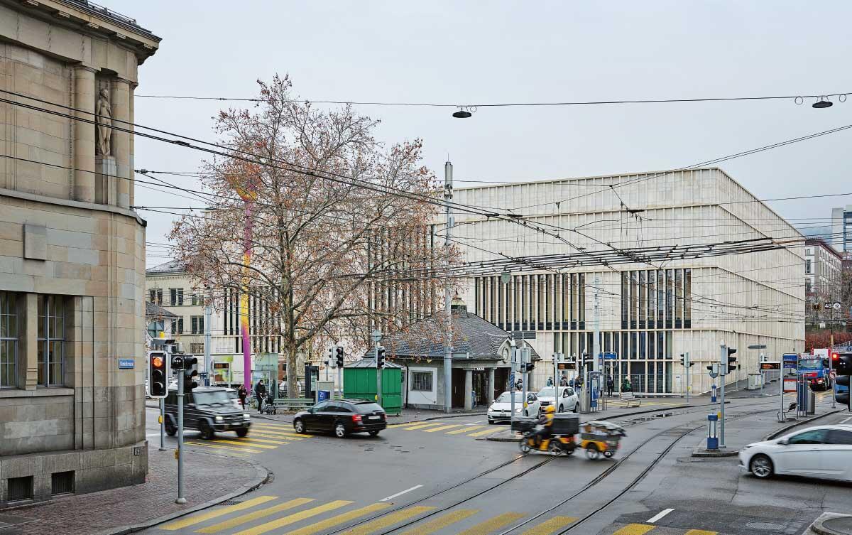 Der Sandstein-Palazzo antwortet auf den Bestandesbau von Karl Moser (links) und verleiht dem Heimplatz mit seinem lebhaften Verkehrsgeschehen eine würdevolle Platzwand. Über der Platzmitte zwinkert die bunte Leuchtskulptur von Pipilotti Rist. Bild: Noshe