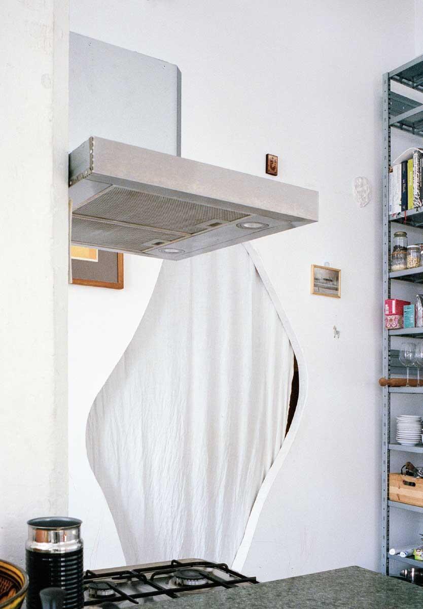 Zwei Öffnungen dienen als Zugang zum hinteren Raum. Sie könnten unterschiedlicher nicht sein: Eine so unsichtbar wie möglich, ein einfaches  Rechteck eingelassen in die Wand, die andere expressiv und einladend, aber versteckt durch ihre Lage. Bild: Bessire Winter