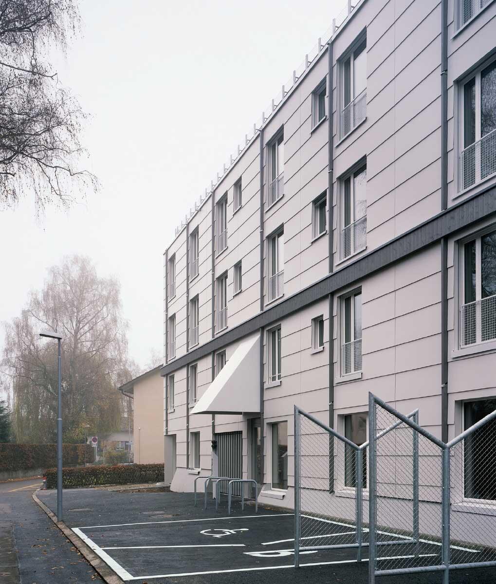 Ein Gesims und unregelmässig verteilte Lisenen auf der hellen Eternitfassade sorgen für Rhythmus, Massstab und Ordnung. Bild: Hélène Binet