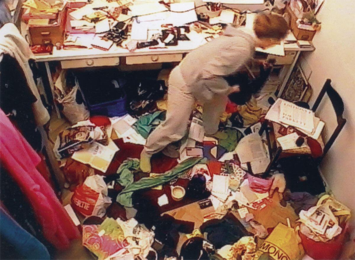 Das Bild stammt aus einer Videoinstallation der deutschen Künstlerin Stephanie Senge. Das 2000 entstandene Video «Aufräumen» dauert vier Stunden: «Ein halbes Jahr räumte ich in meinem Zimmer bewusst nicht mehr auf. Dann installierte ich an der Decke eine Videokamera mit der ich den gesamten Prozess des Aufräumens dokumentierte. Man sieht mich in meinen eigenen Ding-Chaos auf der Suche nach Wertschätzung.»