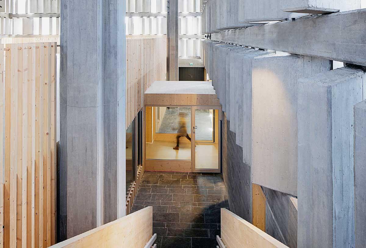 In die geschützte, aber leere brutalistische Kirche Christkönig in Saarlouis setzten die Architekten FlosundK 2018 eine Kita als hölzerne Box.  Bild: Sven Paustian