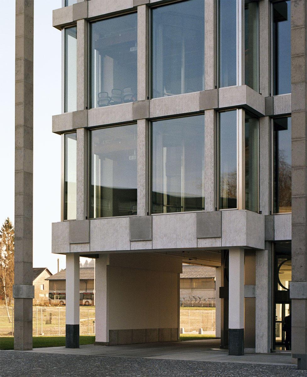 Die Fassade ist auf Pfosten, Riegel und Knoten gefügt; die vorfabrizierten Betonelemente sind aufgeraut und weiss lasiert, während die Knoten schalungsglatt aus dem Werk kommen.