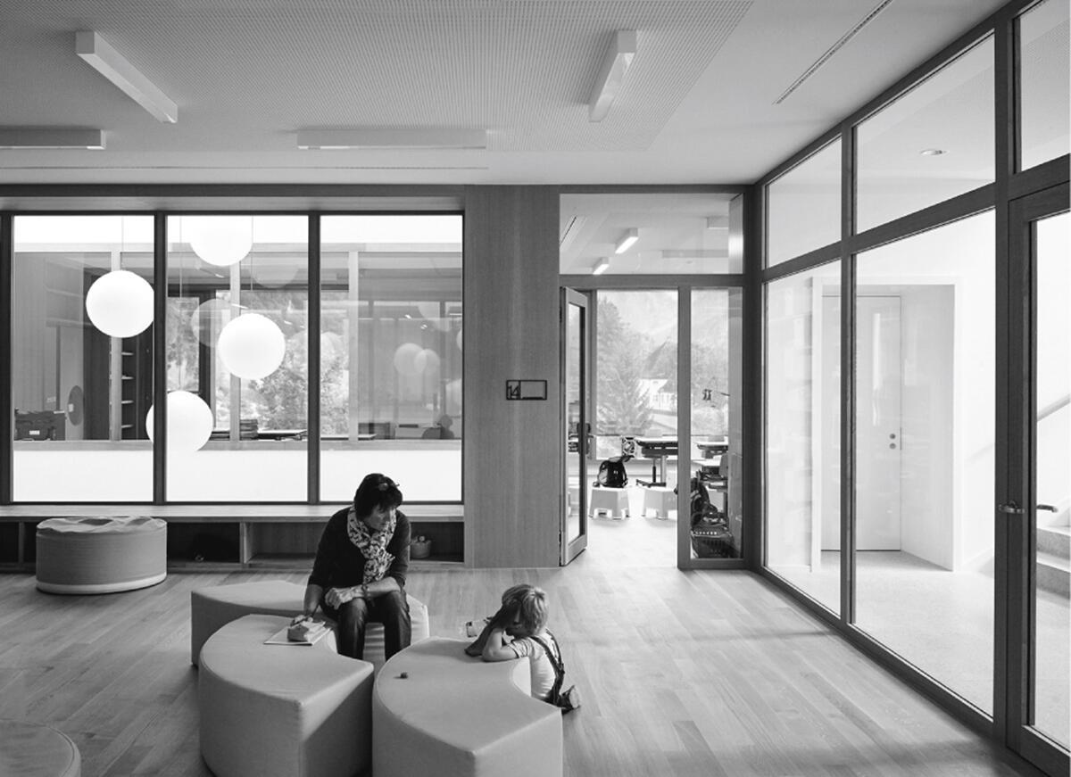 Der Zentralraum in den Obergeschossen ist für den Unterricht verfügbar und erhält Licht über die verglasten Lichthöfe: Primarschulhaus Mühlematt in Engelberg von Rahbaran Hürzeler Architekten.