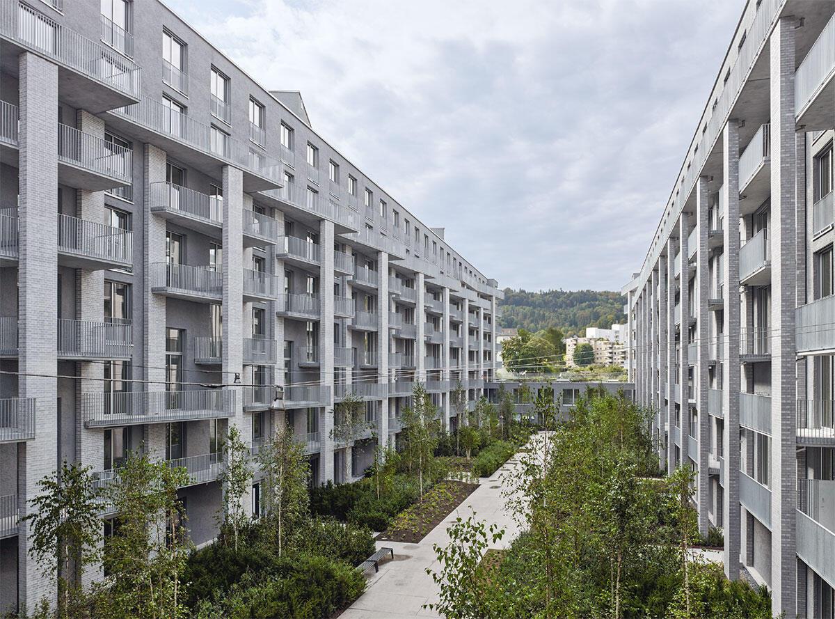 Der Südhof: Hinter der Promenadenfassade verbirgt sich ein enger Innenhof mit dich- tem Pflanzrelief; Vorgärten schützen vor Einblicken: Freilager Zürich. Bild: Georg Aerni