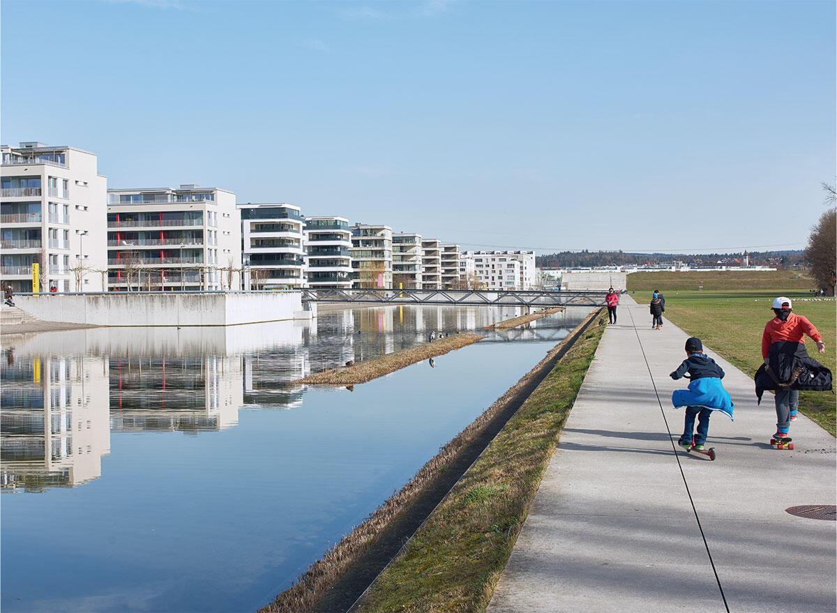 Weite der Landschaft: An den künstlichen See, der hauptsächlich von Meteorwasser gespeist wird, stossen die Zeilen der 1. (Hintergrund) und 2. Bauetappe des Quartiers Glattpark. Im Hintergrund verdeckt der Lärmschutzwall der Autobahn den Kern von Opfikon.