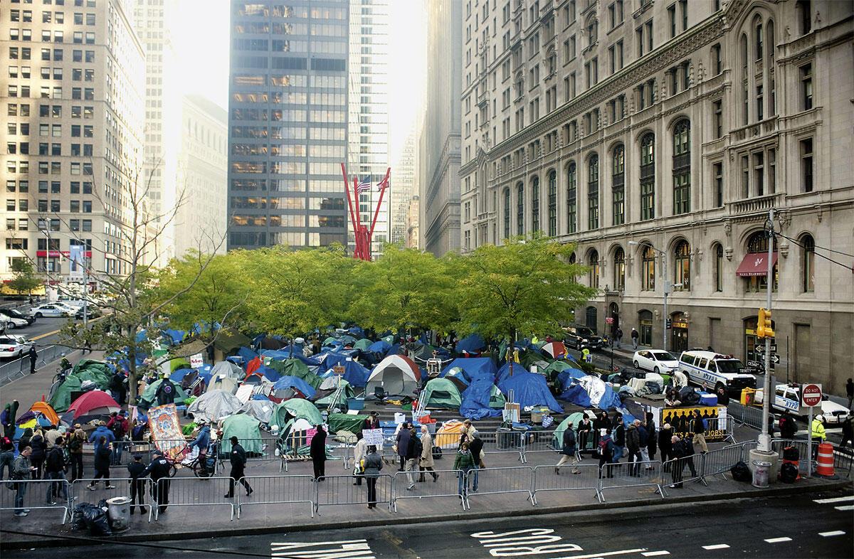 Der Zuccotti Park im Financial District von Manhatten, New York, ist ein «Privatly-Owned-Public-Space», der Anfang der 1970er-Jahre im Zusammenhang mit dem Neubau des Hochhauses von U.S. Steel als Kompensation für zusätzliche Höhe entstand. Im Herbst 2011 wurde der Park zwei Monate lang von den Occupy-Wallstreet-Aktivisten in Beschlag genommen und damit im wahrsten Sinne des Wortes als öffentlicher Raum genutzt; die Aufnahme zeigt den Park am 4. November 2011.