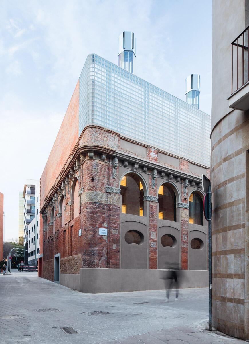 Die neubarocke Pfeilerfassade auf der Südostseite der Cristalleries Planell trägt einen Aufsatz aus Glasbausteinen, darüber ragen die Solarkamine hervor, die das Klima des Gebäudes regulieren. Bild: Adrià Goula