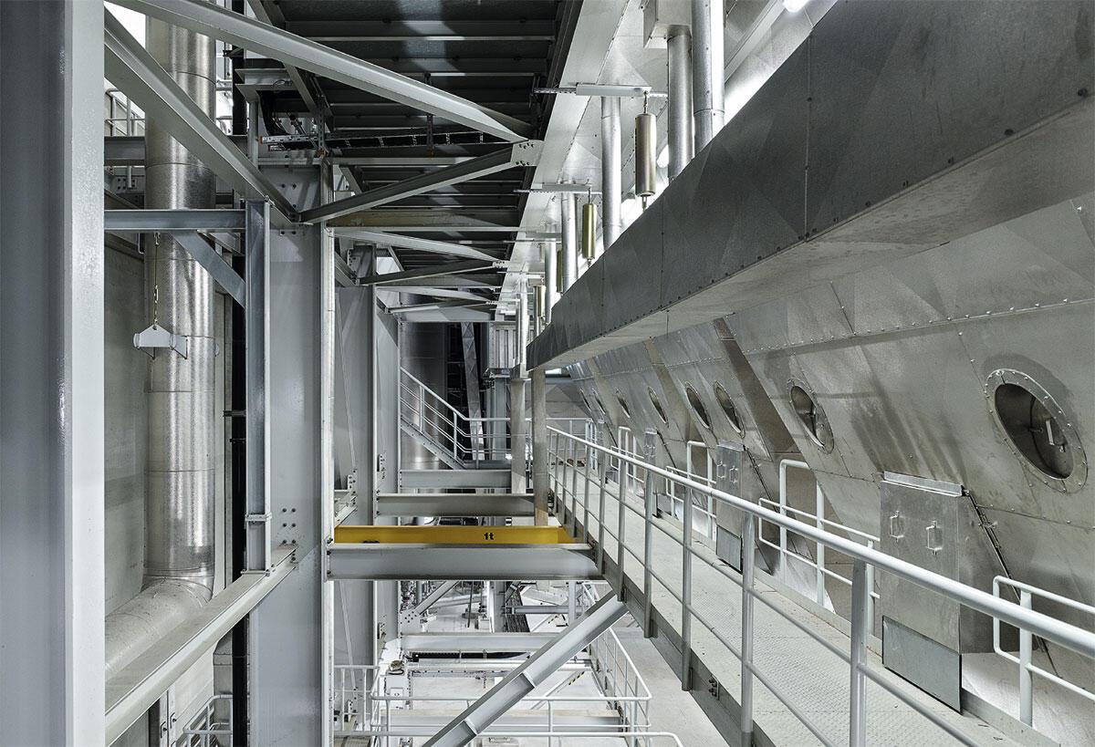 Energiezentrale Forsthaus Bern: Die technischen Einbauten, Stege, Treppen, Geländer und Türen sind alle in derselben Farbe gestrichen. RAL 7035 Lichtgrau vereint in sich die «Naturfarben» der unzähligen technischen Apparaturen.