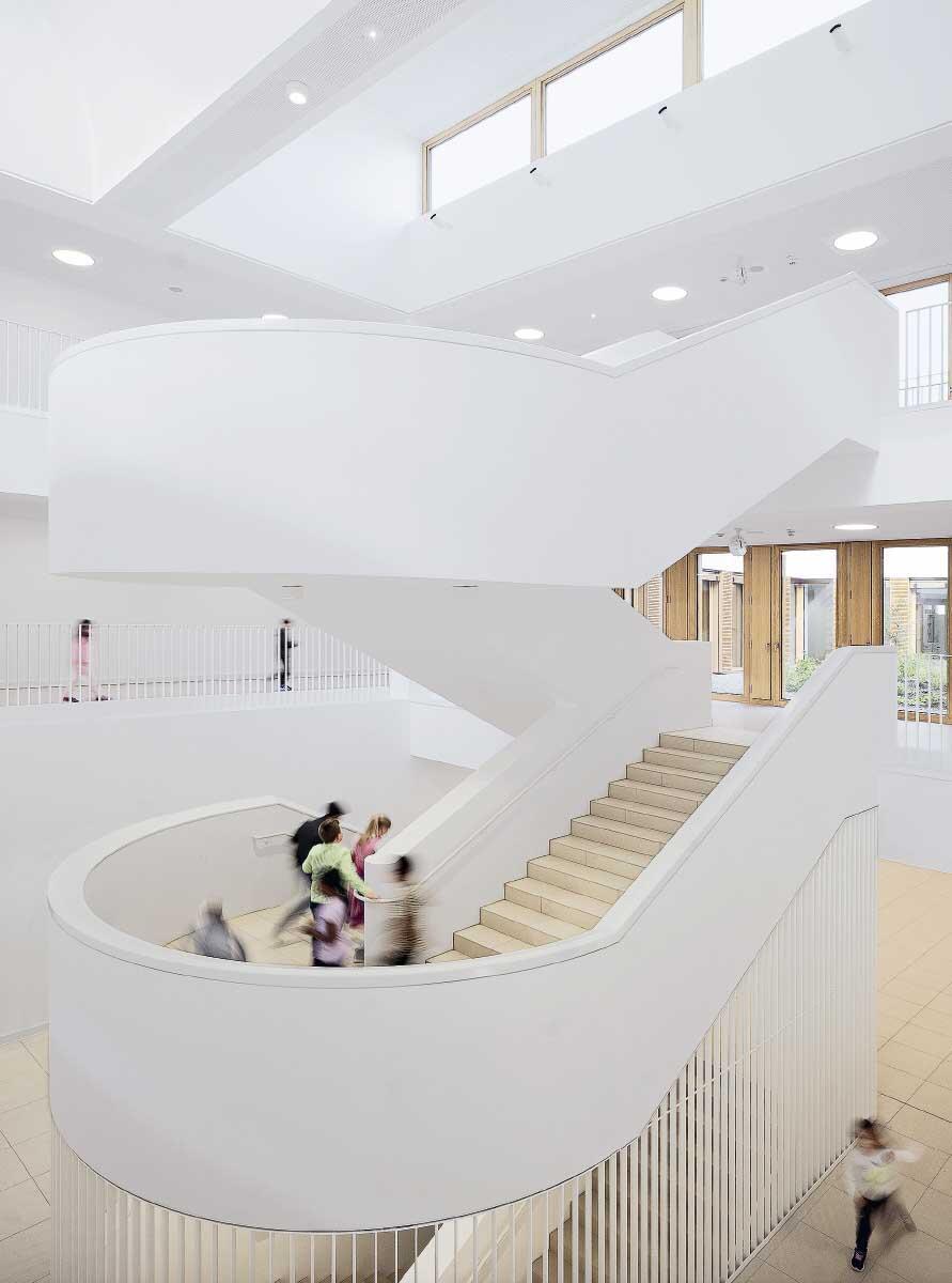 Reines Weiss und für einen Modulbau ungewöhnliche Raumproportionen zeichnen das zentrale Treppenhaus aus. Bild: Adolf Bereuter