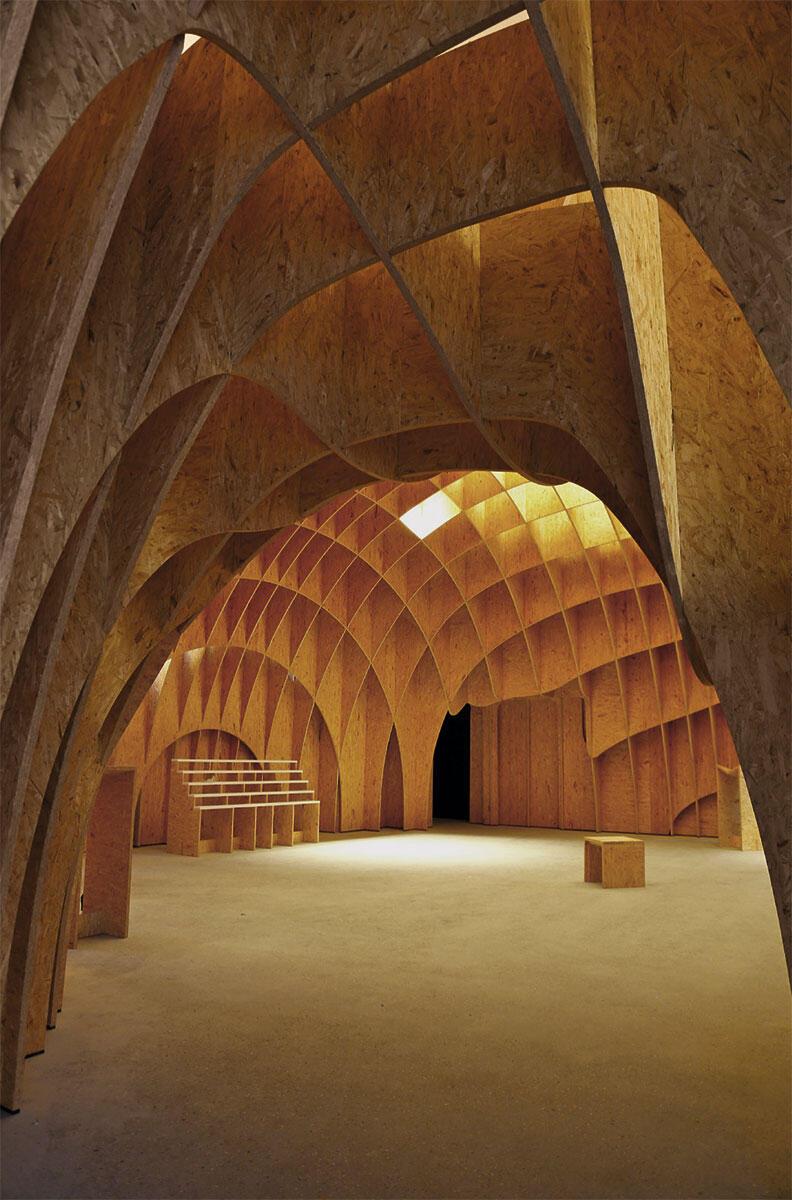 Im Kontrast zum scharf geschnittenen Äusseren zeigt sich der Innenraum als weiches Kuppelgewölbe aus Holz.