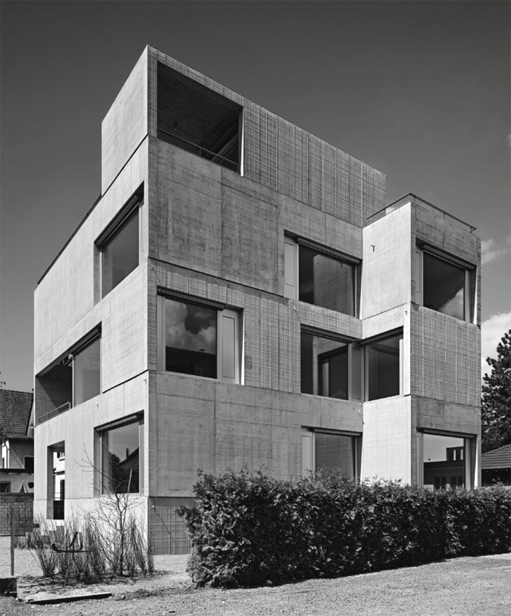 Das Zusammenspiel von Texturen, Öffnungen sowie horizontalen und vertikalen Volumenerweiterungen erzeugt skulpturale Wirkung: Mehrfamilienhaus in Uster von Wild Bär Heule Architekten, Zürich.