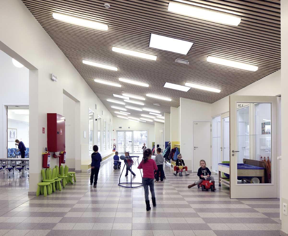 Zahlreiche innere Fenster und Wandöffnungen erweitern die Schulbereiche funktional und optisch: selbst im Speisesaal der Kindergartenkinder im Erdgeschoss oder deren breitem Verteilflur. Bild: Filip Dujardin