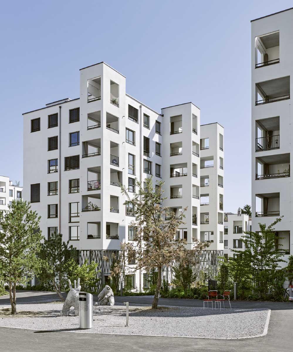 Balkone als Aussenzimmer und intensiv gestaltete Freiräume sorgen für eine lebhafte Gliederung im Siedlungsinneren. Hohe Scheibenhäuser schliessen den Strassenraum. Bild: Georg Aerni