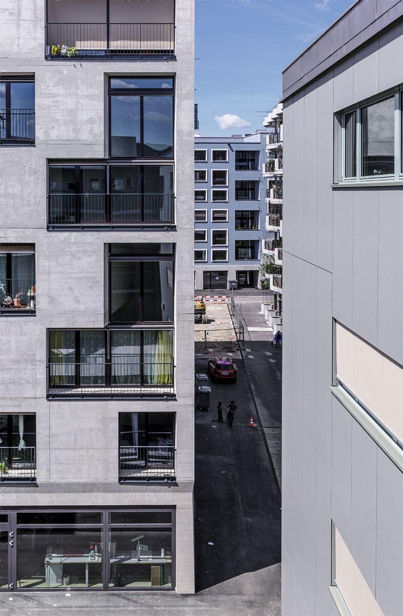 Hunziker-Areal in Zürich: Blick von Osten am Haus G (mit den doppelgeschossigen Einschnitten) vorbei auf die blaue Front von Haus E. Architektur Haus G: pool Architekten, Zürich. Architektur Haus E: Müller Sigrist Architekten, Zürich.