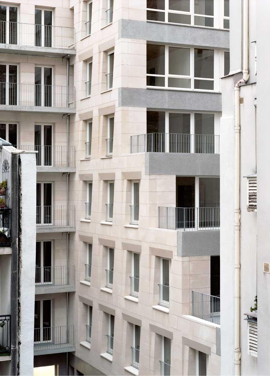Im Pariser Wohnhaus von Barrault Pressacco bestehen Hof- wie Strassenfassade aus tragenden Natursteinblöcken mit facettierten Fensterleibungen. Über den Terrassen übernehmen Stürze aus geschliffenem Beton die grössere Spannweite. Bild: Maxime Delvaux