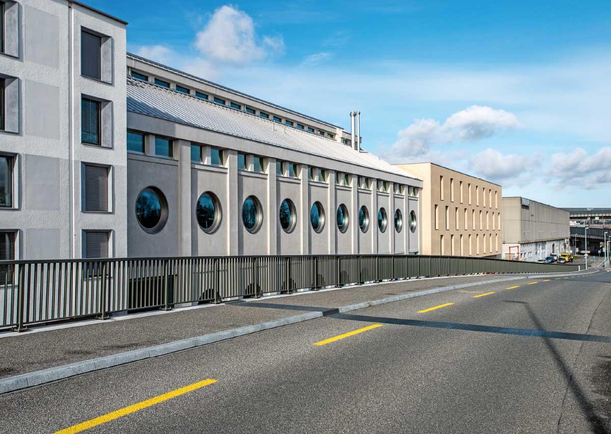 Die Immobilien an der lärmbelasteten Auffahrt zur Autobahn entwickelte die Stiftung Habitat selbst. Die runden Fenster des Silos sind hier festverglast. Bild: Lukas Schwabenbauer