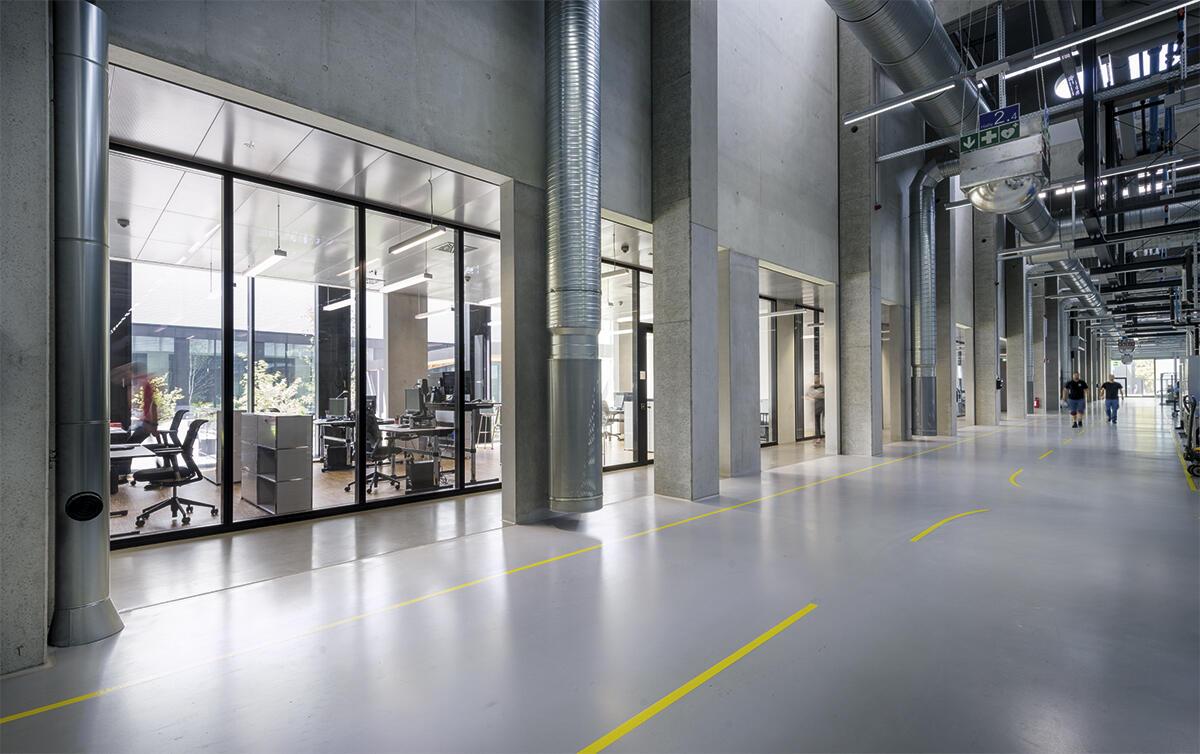 Direkt angrenzend an die Shedhallen liegen die Büros und Besprechungsräume der Ingenieure. Von hier aus haben sie die Produktion im Blick. Diese Zonen sind strukturell zwischen die Hallen eingepasst. HAWE in Kaufbeuren von Barkow Leibinger Architekten.
