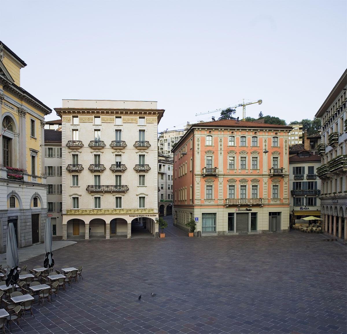 Die denkmalgeschützte, 200-jährige Fassade unter ihresgleichen an der Piazza Riforma in Lugano (links, in Frontansicht und mit hellem Putz). Die aktuelle Erscheinung erhielt sie Anfang des 20. Jahrhunderts durch den Tessiner Architekten Giuseppe Pagani.