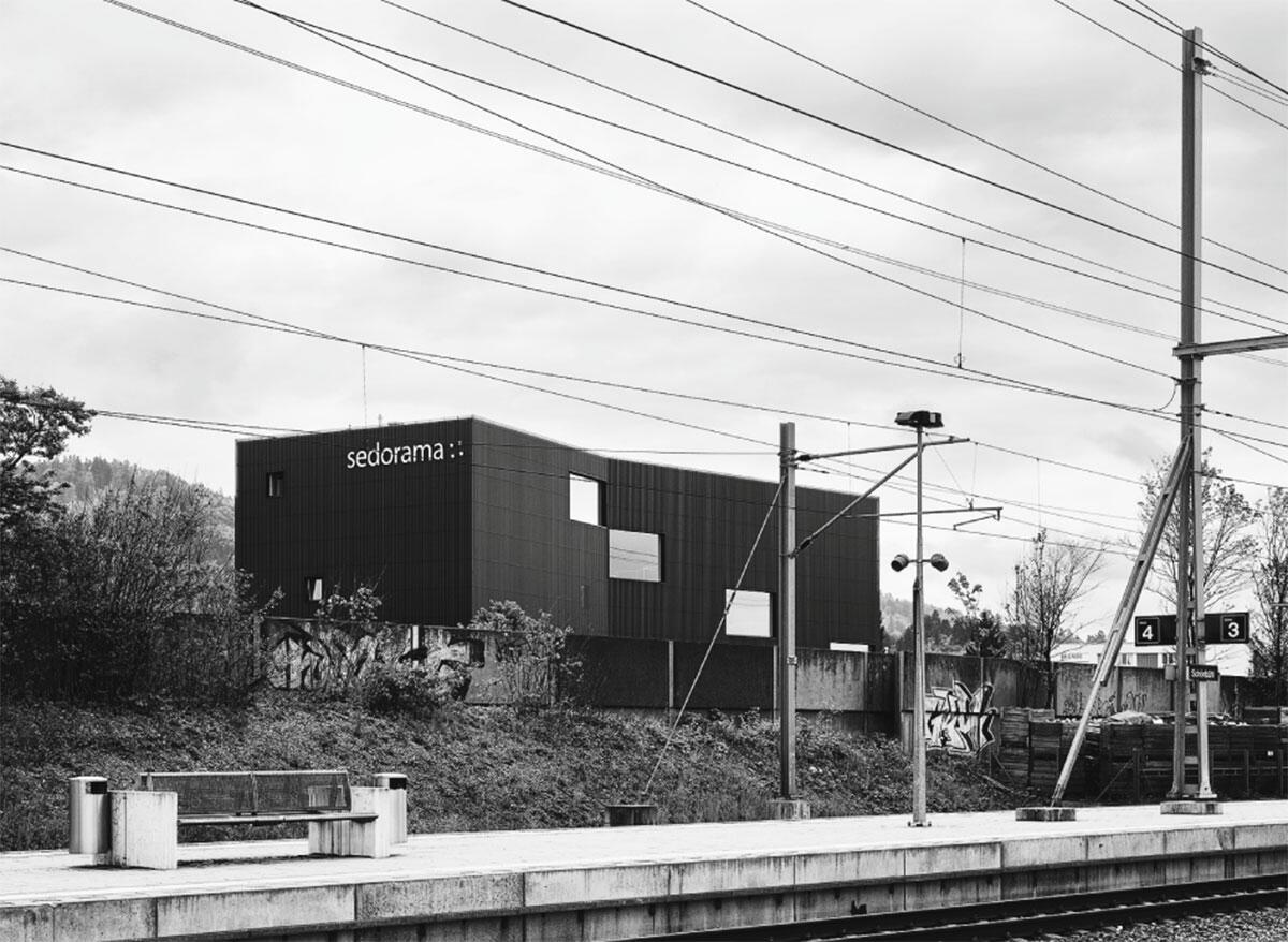 Konkav geschnittener Kubus an Bahn und Autobahn: Hauptsitz Sedorama in Bern von EM2N Architekten.