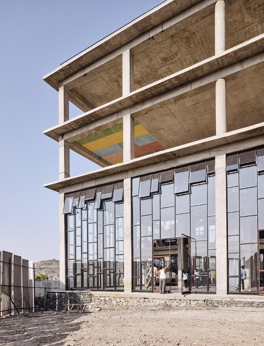 Oben noch Rohbau mit Farbmustern an der Decke, die Eingangstür wird gerade gestrichen, und hinter dem Glas wird die zukünftige Bibliothek zwischenzeitlich als Turnhalle genutzt. Bild: Ariel Huber
