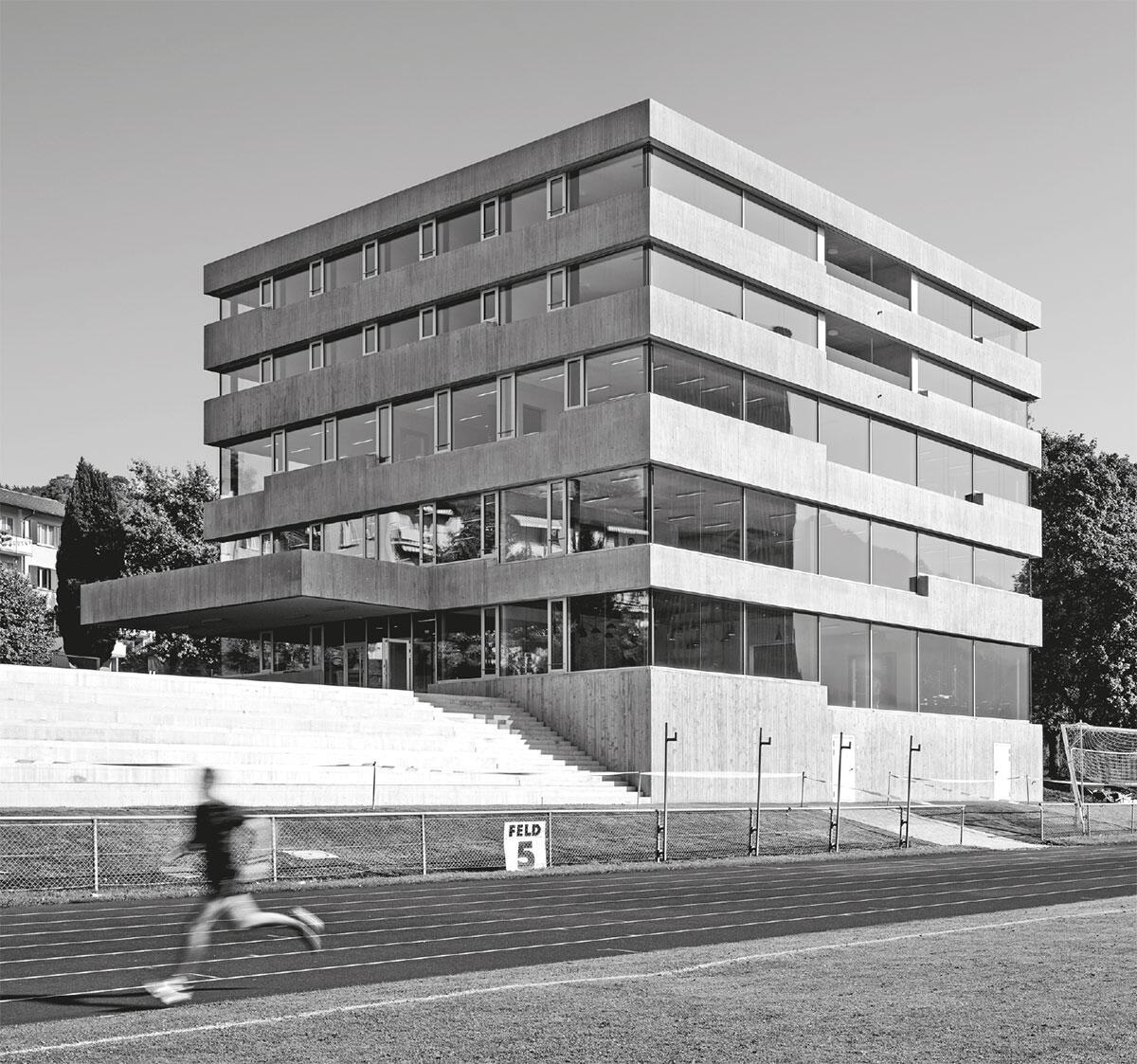 Multifunktionale Nutzungen sind zum einprägsamen Zeichen aufgeschichtet. Rohe Sichtbetonbänder umgürten den Solitär: Pilatus-Akademie in Luzern von Lütolf und Scheuner Architekten