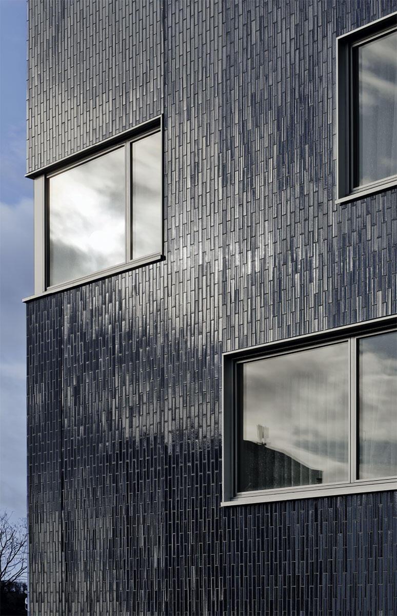 Chebbi Thomet Architektinnen: Alterswohnungen Hirzenbach, Zürich 2002 – 08; Fassadenausschnitt mit glänzender Klinkerverkleidung und über Eck laufender Verglasung.