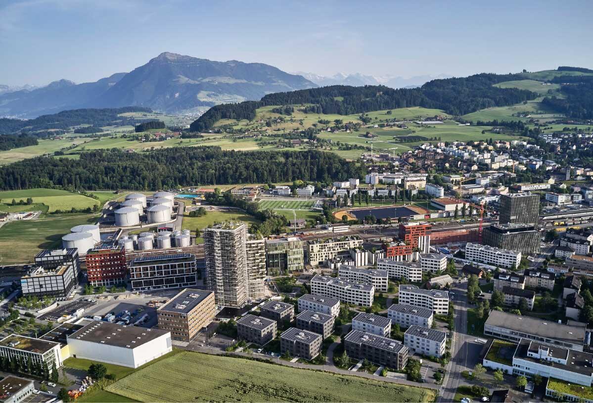 Neben Tanklager und Sportanlage findet sich auch das alte Dorfzentrum von Rotkreuz südlich der Gleise. Nördlich des Bahnhofs ist das neue Quartier Suurstoffi mit seinen markanten Türmen für das Wohnen (links) und die Hochschule Luzern HSLU (rechts) gewachsen. Bild: Zug Estates