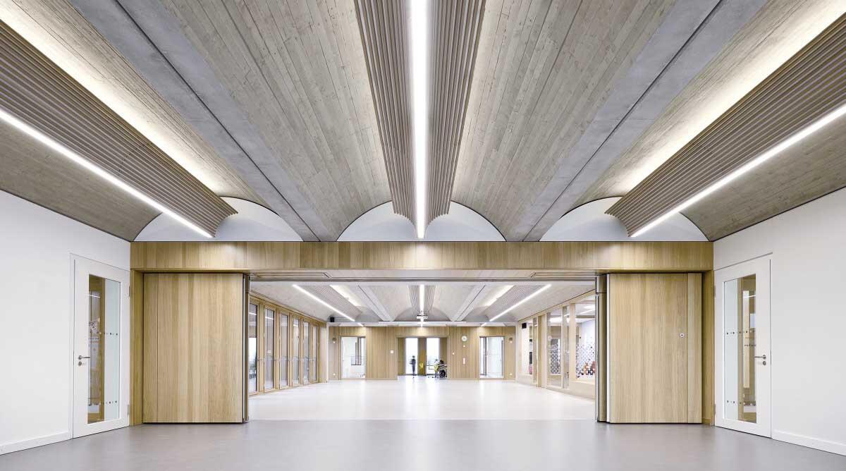 Für die Eingangszone im Erdgeschoss kommen Sondermodule zum Einsatz; sie ist auch für grössere Zusammenkünfte der Schule ausgelegt. Bild: Brigida González
