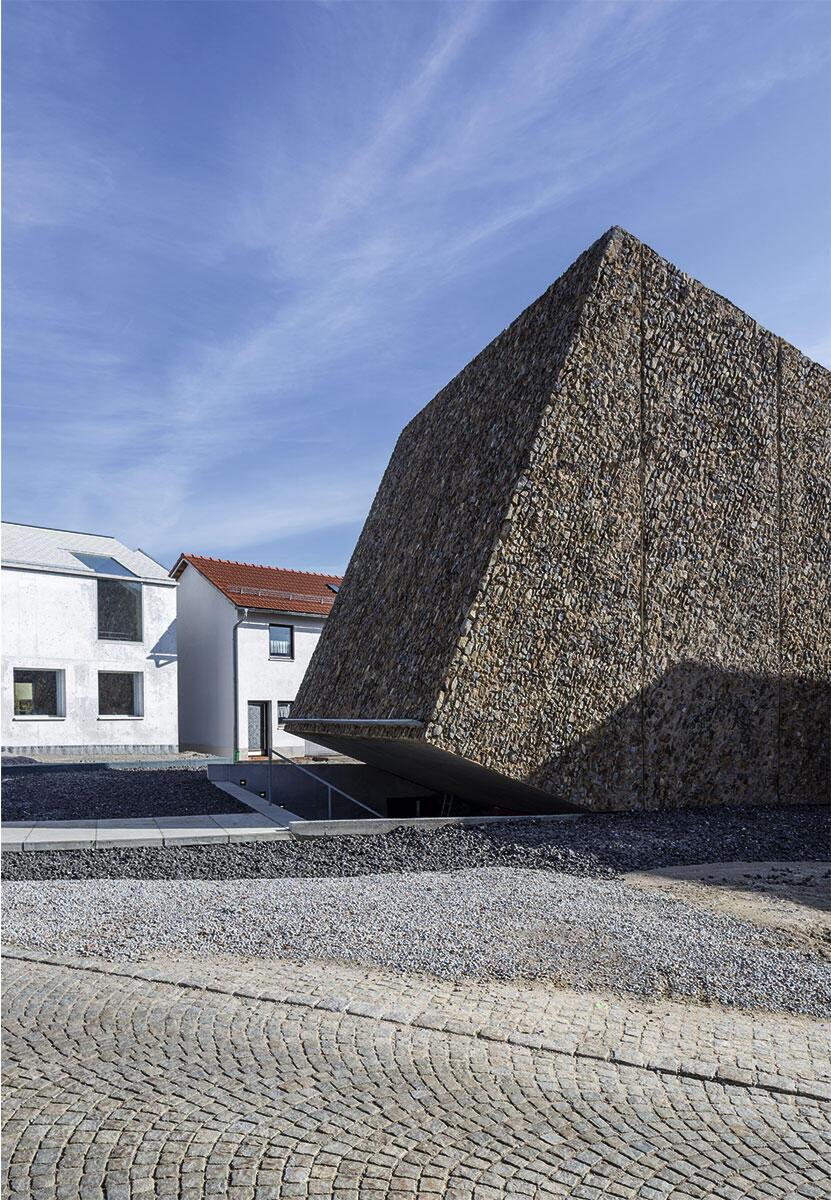 Einem Meteoriten gleich landete ein felsig schroffer Kubus mitten auf dem Dorfplatz von Blaibach. Einzig ein klaffender Spalt bietet einen Hinweis auf den Eingang ins Konzerthaus.