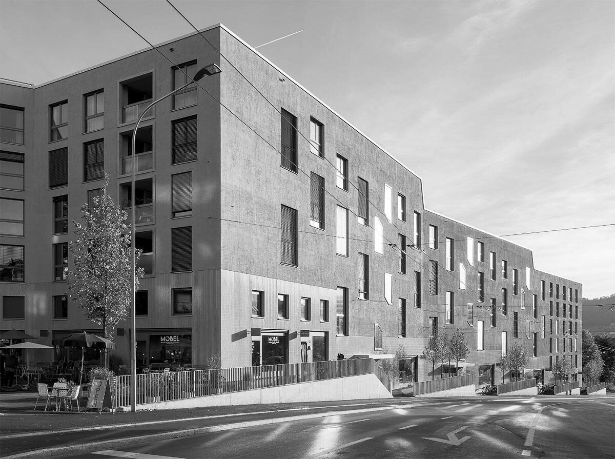 Spektakuläre, zweigeschossige Wohnküchen hinter grossen Fenstern in der Minergie A-Siedlung Kronenwiese minimieren Fassadenfläche an der lärmigen Strasse. Bild: Roman Keller