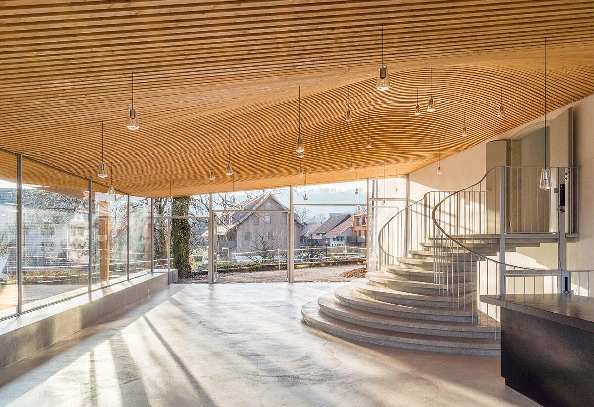 Die kuppelartige Wölbung der hölzernen Decke gibt der elegant geschwungenen Treppe und ihren Benutzern den nötigen Raum und trägt dazu bei, das Foyer zu zentrieren.